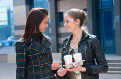 Two girls on a street with coffee Royalty Free Stock Image