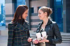Two girls on a street with coffee Royalty Free Stock Photography
