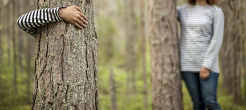 Two girls in striped clothes hugging tree trunks Stock Photo