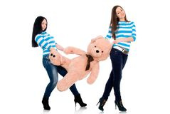 Two girls in striped vests with a teddy bear Stock Photos