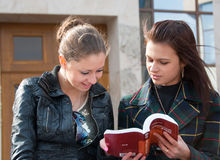 Two girls students read textbook outdoors Royalty Free Stock Image