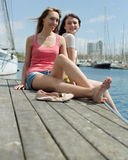 Two girls students resting on the sea berth royalty free stock photo