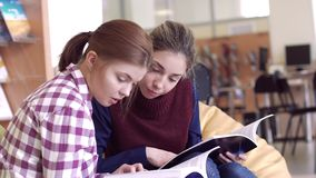 Two girls studying scientific books in library. While preparing research stock footage