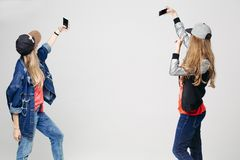 Two girls in stylish clothing taking selfie on smartphone. royalty free stock images