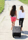 Two girls with suitcase Stock Images