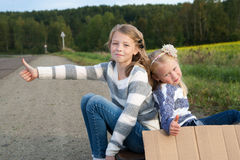 Two girls with suitcase standing about road Royalty Free Stock Image