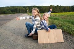 Two girls with suitcase standing about road Stock Photos