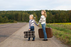 Two girls with suitcase standing about road Royalty Free Stock Photo