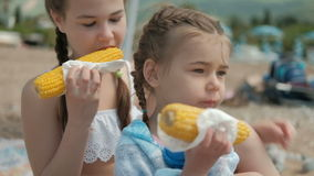 Two girls in the summer eat boiled corn in a napkin. Two girls in the summer eat boiled corn in a napkin on beach. The children are enjoying a delicious yellow stock video footage