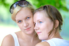 Two girls in the summer park one looks into camera Royalty Free Stock Photo