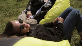Two girls in sunglasses relaxing on yellow beanbags on green grass, smile. Summer festival. Rest. Slow motion stock footage