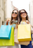 Two girls in sunglasses with shopping bags in ctiy Stock Photos