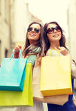 Two girls in sunglasses with shopping bags in ctiy Stock Images