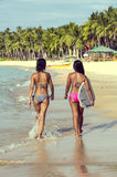 Two girls with a surfboard. On the beach Royalty Free Stock Photography