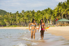 Two girls with a surfboard. On the beach Stock Image