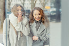 Two girls surprised looking at show-window Stock Image