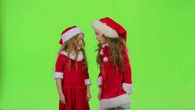 Two children girls swear and argue, they are in colorful costumes. Green screen. Slow motion. Two girls swear and argue the girls, they are ready to celebrate in stock video