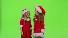 Two children girls swear and argue, they are in colorful costumes. Green screen. Two girls swear and argue the girls, they are ready to celebrate in colorful stock footage