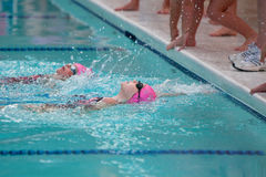 Two Girls Swimming Backstroke Reach For Wall Royalty Free Stock Photos