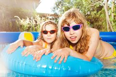 Two girls swimming in the pool with  rubber ring. Close-up portrait of two girls in sunglasses swimming in the inflatable pool with blue rubber ring stock photos