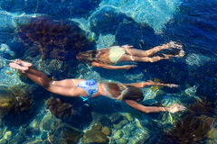 Two girls swimming under water stock image