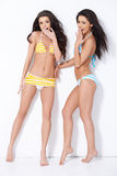 Two girls in swimsuits. Having fun over white background Stock Images