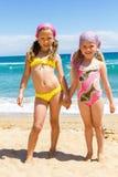 Two girls in swimwear on beach. Full length Portrait of two girls in swimwear standing on beach Stock Photo