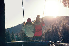 Two girls on a swing, couple and sunset. Together Royalty Free Stock Photos