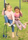 Two girls on swing. Two kids sitting on one swing on playground - one little girl in pink socks and second barefoot removing her last sock Royalty Free Stock Photos