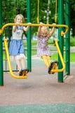 Two girls swinging on playground Stock Images