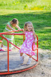 Two girls swinging on playground Royalty Free Stock Images