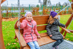 Two girls swinging on playground Royalty Free Stock Image