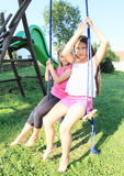Two girls swinging on swing Stock Photo
