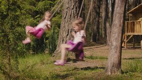 Two girls are swinging on swings in the forest. Two adorable girls are swinging on swings in a summer forest stock footage