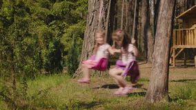 Two girls are swinging on swings in the forest. Two adorable girls are swinging on swings in a summer forest stock video footage