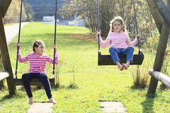 Two girls swinging on two swings. Two smiling kids - little girls playing and swinging on two swings Royalty Free Stock Photography