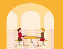 Two girls at a table. Two girls sitting at a table in a bistro Stock Photo