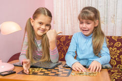 Two girls at table collected montki one cries, the other laughs at it Stock Images