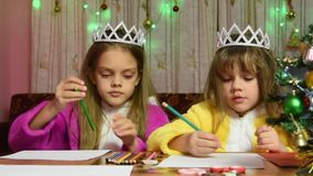 Two girls at the table draw, funny one selects desired color pencil stock video