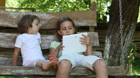 Two girls with tablet computer sit on the swing bench. Two little girls with tablet computer sit on the swing bench. Two sisters with tablet PC sit on the swing stock video footage