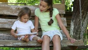 Two girls with tablet computer sits on the swing bench. Two little girls with tablet computer sits on the swing bench. Two sisters with tablet PC sits on the stock video footage