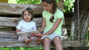 Two girls with tablet computer sits on the swing bench. Two little girls with white tablet computer sits on the swing bench. Female with tablet computer stock footage
