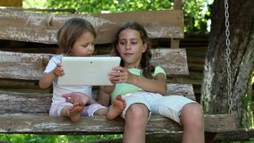 Two girls with tablet computer sits on the swing bench. Two sisters with tablet PC sits on the swing bench. Two little girls with tablet computer sits on the stock video