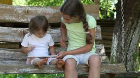 Two girls with tablet computer sits on the swing bench. Two sisters with tablet PC sits on the swing bench. Two little girls with white tablet computer sits on stock video footage