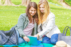 Two girls with tablet. In the park Stock Photography