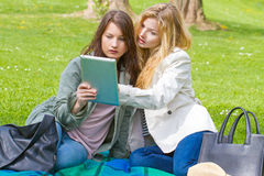 Two girls with tablet. In the park Stock Photo