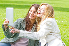Two girls with tablet Stock Images