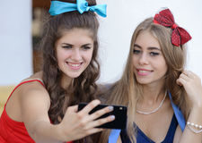 Two girls take pictures on your phone Royalty Free Stock Photography