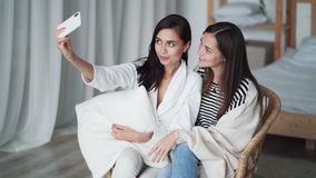 Two girls take selfie on phone, posing, show gesture of peace, smiling at home. Sisters take photo as keepsake stock footage