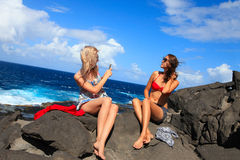 Two girls taking photo on the beach in summer holidays and vacat Royalty Free Stock Photo